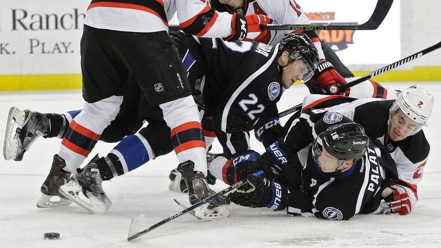 Tampa Bay Lightning left wing Ondrej Palat (18), of the Czech Republic, and right wing Erik Condra (22) get taken down by New Jersey Devils defenseman John Moore during the second period of an NHL hockey game Saturday, April 2, 2016, in Tampa, Fla. (AP Photo/Chris O'Meara)