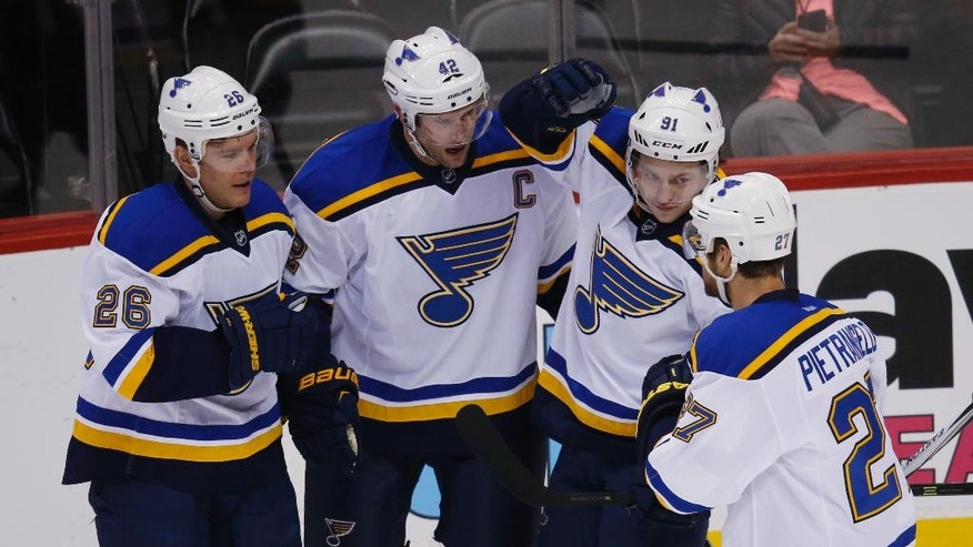St. Louis Blues center David Backes, second from left, celebrates scoring a goal with, from left, center Paul Stastny, right wing Vladimir Tarasenko, of Russia, and defenseman Alex Pietrangelo against the Colorado Avalanche in the first period of an NHL hockey game, Sunday, April 3, 2016, in Denver. (AP Photo/David Zalubowski)