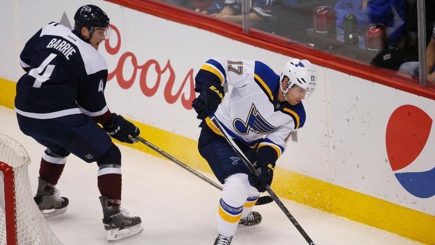 St. Louis Blues left wing Jaden Schwartz, right, tries to wrap around the net for a shot past Colorado Avalanche defenseman Tyson Barrie in the first period of an NHL hockey game, Sunday, April 3, 2016, in Denver. (AP Photo/David Zalubowski)