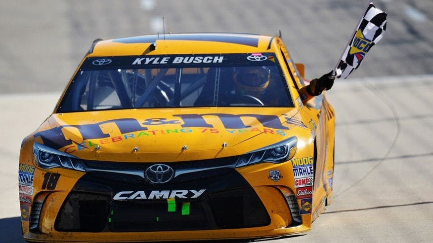 MARTINSVILLE, VA - APRIL 03: Kyle Busch, driver of the #18 M&M's 75th Anniversary Toyota, celebrates with the checkered flag after winning the NASCAR Sprint Cup Series STP 500 at Martinsville Speedway on April 3, 2016 in Martinsville, Virginia. (Photo by Drew Hallowell/Getty Images)
