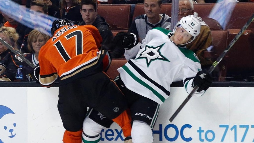 Anaheim Ducks center Ryan Kesler, left, hits Dallas Stars center Cody Eakin, right, into the boards during the first period of an NHL hockey game in Anaheim, Calif., Sunday, April 3, 2016. (AP Photo/Alex Gallardo)