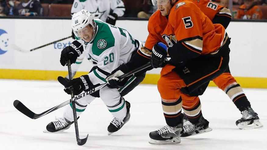 Dallas Stars center Cody Eakin (20) battles Anaheim Ducks defenseman Korbinian Holzer (5), of Germany, to get to the puck during the first period of an NHL hockey game in Anaheim, Calif., Sunday, April 3, 2016. (AP Photo/Alex Gallardo)