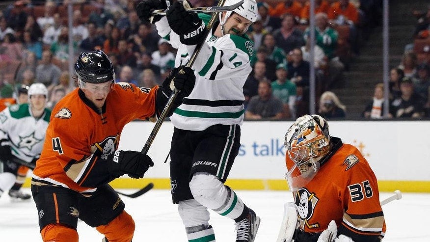 Anaheim Ducks goalie John Gibson, right, covers up the puck as defenseman Cam Fowler, left, defends against Dallas Stars left wing Jamie Benn, center, during the first period of an NHL hockey game in Anaheim, Calif., Sunday, April 3, 2016. (AP Photo/Alex Gallardo)
