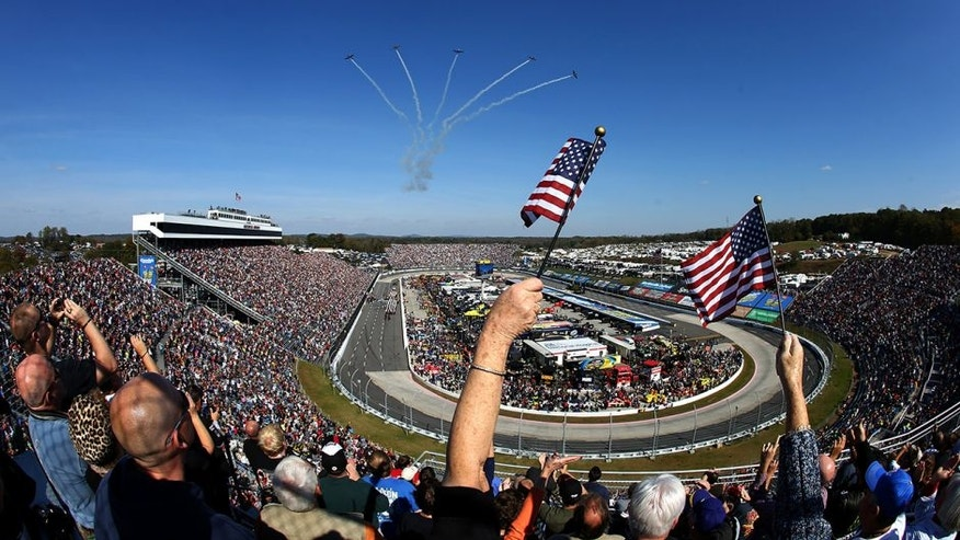 MARTINSVILLE, VA - OCTOBER 27: Fans wave American flags as five CJ-6A's from Affordable Warbirds perform a flyover prior to the NASCAR Sprint Cup Series Goody's Headache Relief Shot 500 Powered By Kroger at Martinsville Speedway on October 27, 2013 in Martinsville, Virginia. (Photo by Streeter Lecka/Getty Images)