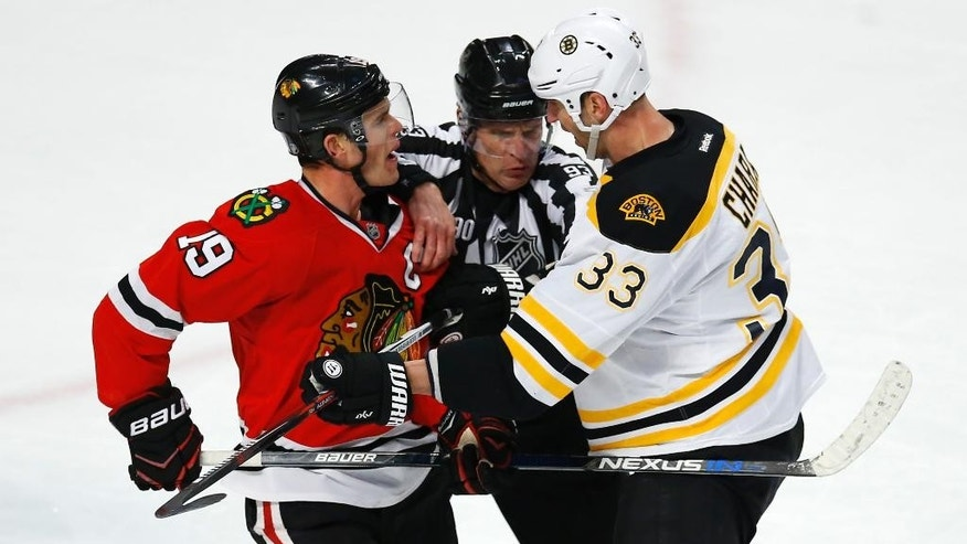 Chicago Blackhawks center Jonathan Toews (19) and Boston Bruins defenseman Zdeno Chara (33) are separated by linesman Brian Murphy (93) during the first period of an NHL hockey game Sunday, April 3, 2016, in Chicago. (AP Photo/Jeff Haynes)