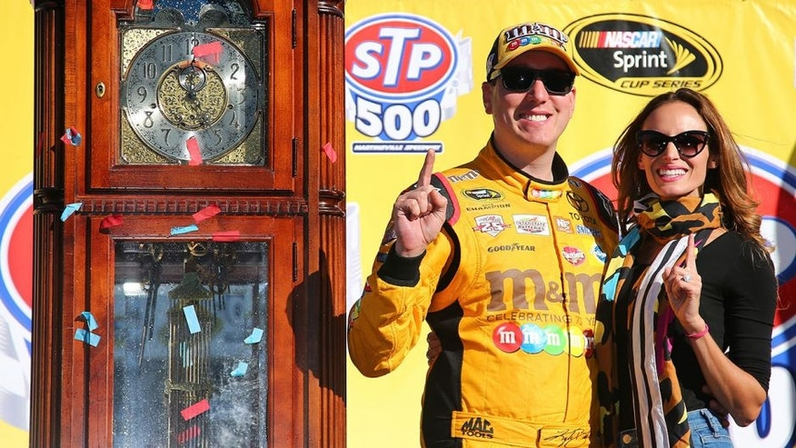 MARTINSVILLE, VA - APRIL 03: Kyle Busch, driver of the #18 M&M's 75th Anniversary Toyota, poses for a photo with his wife Samantha in Victory Lane ater winning the NASCAR Sprint Cup Series STP 500 at Martinsville Speedway on April 3, 2016 in Martinsville, Virginia. (Photo by Sarah Crabill/Getty Images)