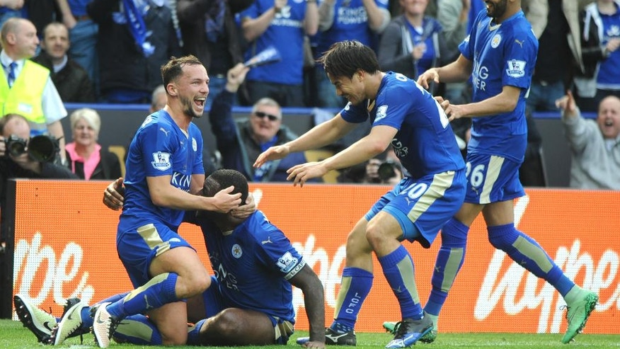Leicester's Wes Morgan, 2nd left, celebrates after scoring with Leicester's Daniel Drinkwater, left, Leicester's Shinji Okazaki, 2nd right, and Leicester's Riyad Mahrez during the English Premier League soccer match between Leicester City and Southampton at the King Power Stadium in Leicester, England, Sunday, April 3, 2016. (AP Photo/Rui Vieira)