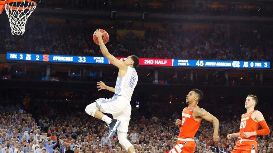 North Carolina guard Marcus Paige (5) leaps toward the goal as Syracuse forward Michael Gbinije (0) gives chase during the second half of the NCAA Final Four tournament college basketball semifinal game Saturday, April 2, 2016, in Houston.
