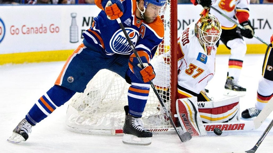 Calgary Flames goalie Joni Ortio (37) makes a save on Edmonton Oilers' Taylor Hall (4) during the second period of an NHL game in Edmonton, Alberta, on Saturday, April 2, 2016. (Jason Franson/The Canadian Press via AP)
