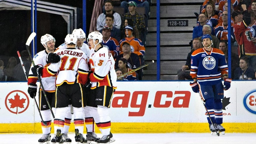 Calgary Flames celebrate a goal as Edmonton Oilers' Adam Pardy (6) skates past during the second period of an NHL game in Edmonton, Alberta, on Saturday, April 2, 2016. (Jason Franson/The Canadian Press via AP)