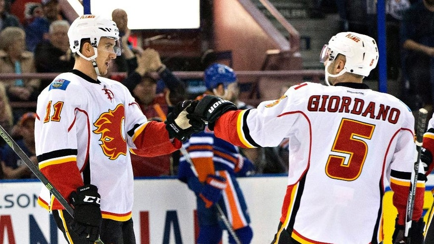 Calgary Flames' Mikael Backlund (11) and Mark Giordano (5) celebrate a goal against the Edmonton Oilers during the first period of an NHL game in Edmonton, Alberta, on Saturday, April 2, 2016. (Jason Franson/The Canadian Press via AP)
