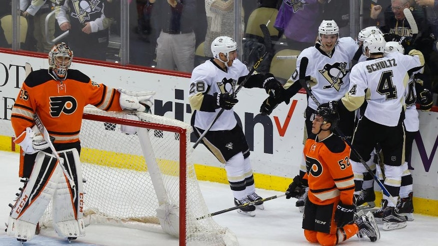 The Pittsburgh Penguins Ian Cole (28), Justin Schultz (4) and Oskar Sundqvist (40) celebrate a goal by teammate Beau Bennett in the first period against Philadelphia Flyers goalie Steve Mason, left, as Flyers' Nick Cousins (52) kneels on the ice during an NHL hockey game, Sunday, April 3, 2016, in Pittsburgh. (AP Photo/Keith Srakocic)