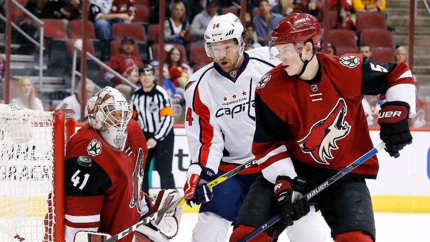 Arizona Coyotes' Mike Smith (41) makes a save off his shoulder as Coyotes' Connor Murphy (5) and Washington Capitals' Justin Williams (14) work for position during the first period of an NHL hockey game Saturday, April 2, 2016, in Glendale, Ariz. (AP Photo/Ross D. Franklin)
