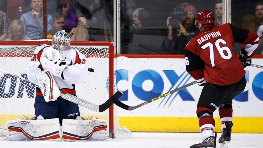 Washington Capitals' Philipp Grubauer (31), of Germany, makes a save on a shot by Arizona Coyotes' Laurent Dauphin (76) during the first period of an NHL hockey game Saturday, April 2, 2016, in Glendale, Ariz. (AP Photo/Ross D. Franklin)