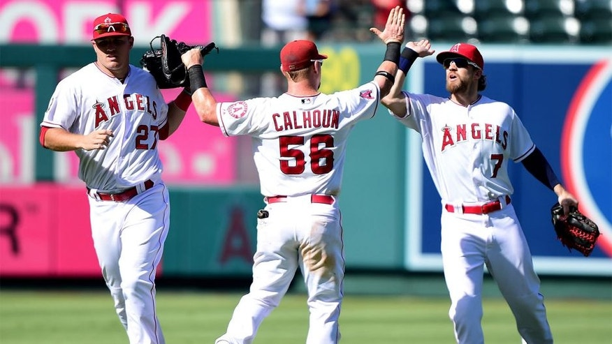 ANAHEIM, CA - SEPTEMBER 27: Kole Calhoun #56 of the Los Angeles Angels celebrates a 3-2 win over the Seattle Mariners with Mike Trout #27 and Collin Cowgill #7 at Angel Stadium of Anaheim on September 27, 2015 in Anaheim, California. (Photo by Harry How/Getty Images)