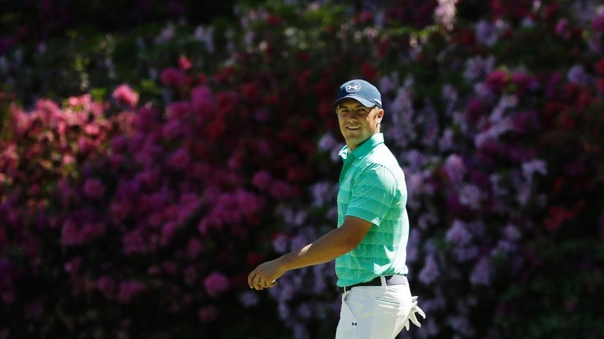 Jordan Spieth looks back to his caddie while on the 13th green during a practice round for the Masters golf tournament, Monday, April 4, 2016, in Augusta, Ga. (AP Photo/Charlie Riedel)