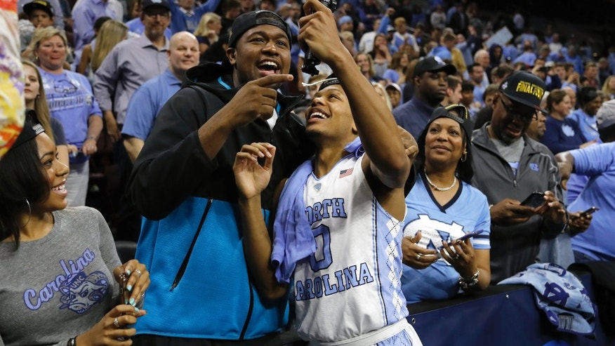 North Carolina's Nate Britt, right, and Villanova's Kris Jenkins celebrate after North Carolina won a regional final men's college basketball game against Notre Dame in the NCAA Tournament, Sunday, March 27, 2016, in Philadelphia. North Carolina won 88-74 to advance to the Final Four. (AP Photo/Matt Rourke)