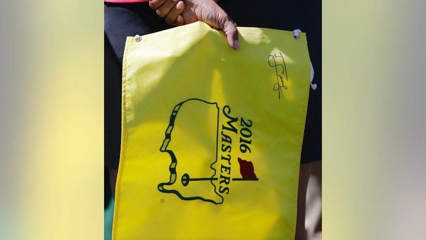 A spectator holds an autograph Masters' flag while watching a practice round for the Masters golf tournament, Monday, April 4, 2016, in Augusta, Ga. (AP Photo/Jae C. Hong)