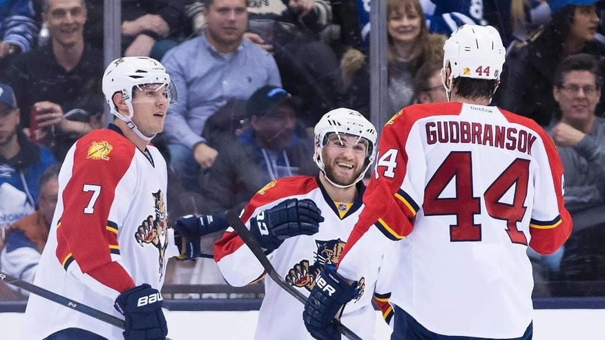 Florida Panthers center Rocco Grimaldi (23) celebrates with teammates Dmitry Kulikov (7) and Erik Gudbranson (44) after scoring against the Toronto Maple Leafs during second period NHL hockey action in Toronto on Monday, April 4, 2016. (Nathan Denette/The Canadian Press via AP) MANDATORY CREDIT