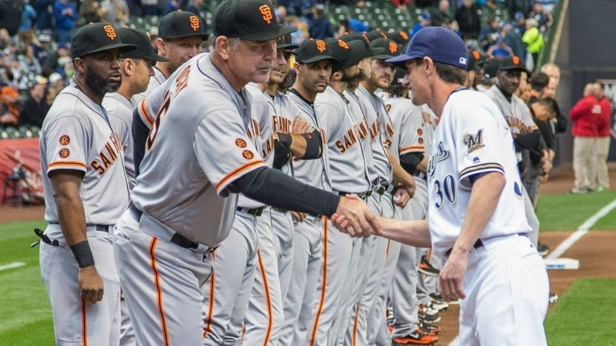 San Fransisco Giants' manager Bruce Bochy, front left, shakes hands with Milwaukee Brewers' manager Craig Counsell before the start of the opening day game.
