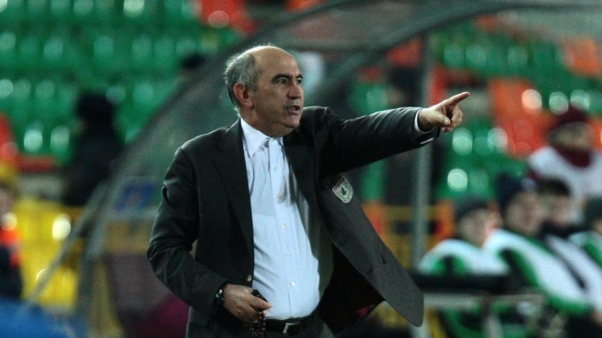 FILE - In this Russia, Thursday Nov. 7, 2013, file photo then Rubin Kazan's team coach Kurban Berdyev gestures during the Europa League group D soccer match against Wigan Athletic in Kazan, Russia.  A narrow escape from relegation one season and then a stunning title challenge the next, provincial club FC Rostov is defying gravity at the top of the Russian Premier League despite crippling financial problems that have led some to suggest it could quite literally be win or bust.  Rostov has the sullen Kurban Berdyev guiding their rise, as a devout Muslim who holds prayer beads in news conferences and treats the media with scorn. (AP Photo/Nikolay Alexandrov, FILE)