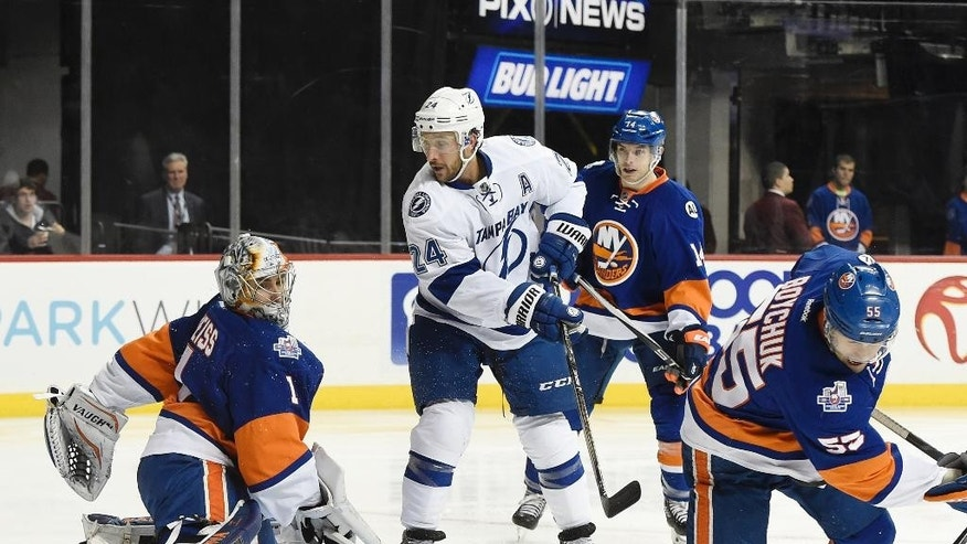 Tampa Bay Lightning right wing Ryan Callahan (24) watches New York Islanders goalie Thomas Greiss (1) block a shot on goal as Islanders defenseman Thomas Hickey (14) and defenseman Johnny Boychuk (55) look on in the first period of an NHL hockey game, Monday, April 4, 2016, in New York. (AP Photo/Kathy Kmonicek)