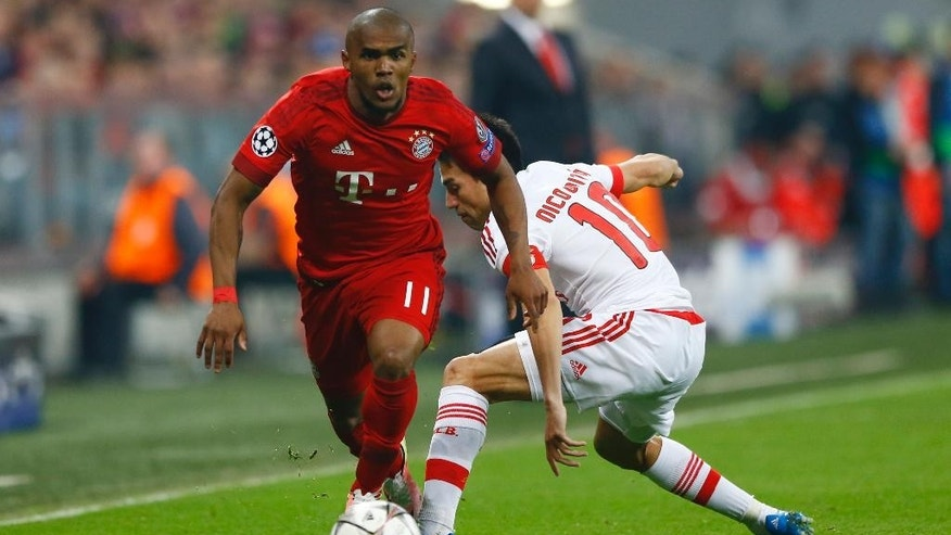 Bayern's Douglas Costa goes past Benfica's Nico Gaitan during the Champions League quarterfinal first leg soccer match between FC Bayern Munich and Benfica Lisbon at the Allianz Arena in Munich, southern Germany, Tuesday, April 5, 2016. (AP Photo/Matthias Schrader)