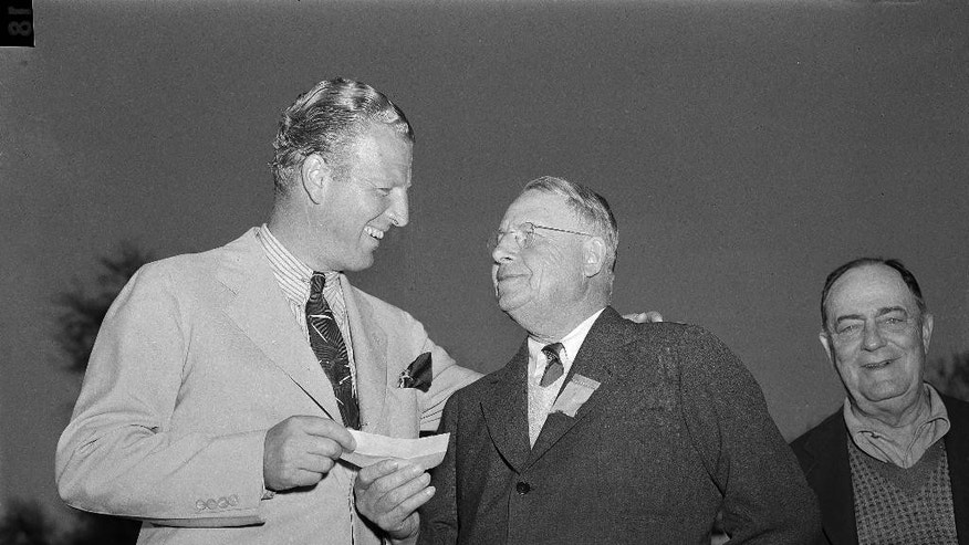 FILE - In this April 6, 1942 file photo, Craig Wood, left, smiles as he accepts accepts a $1,500 check from former Gov. James M. Cox,  of Ohio, as first prize money at the Masters Golf tournament in Augusta, Ga. Wood endured more heartache in the majors than anyone before he finally won. (AP Photo/B.I. Sanders, File)
