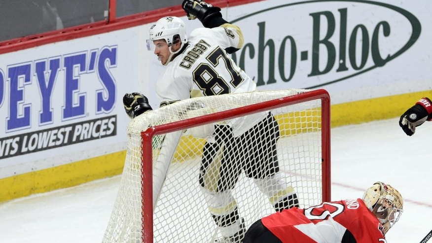 Pittsburgh Penguins center Sidney Crosby celebrates a goal on Ottawa Senators goalie Andrew Hammond during the second period of an NHL hockey game, Tuesday,  April 5, 2016 in Ottawa, Ontario.  (Sean Kilpatrick/The Canadian Press via AP) MANDATORY CREDIT