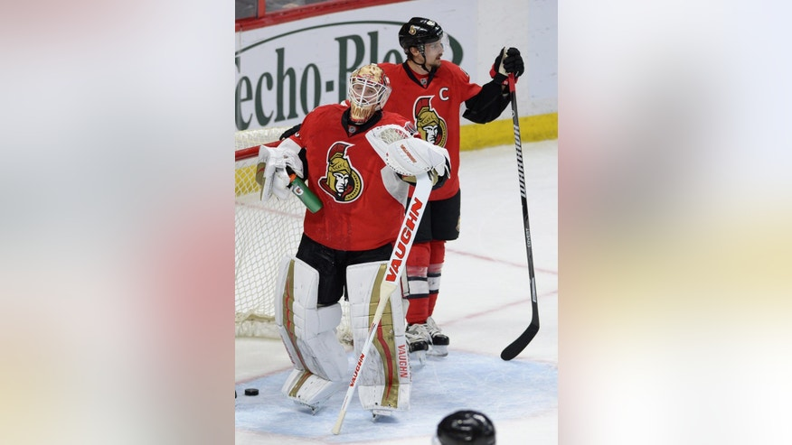 Ottawa Senators goalie Andrew Hammond, left, and defenseman Erik Karlsson react to a goal by Pittsburgh Penguins center Sidney Crosby, not pictured, during the second period of an NHL hockey game, Tuesday,  April 5, 2016 in Ottawa, Ontario.  (Sean Kilpatrick/The Canadian Press via AP) MANDATORY CREDIT