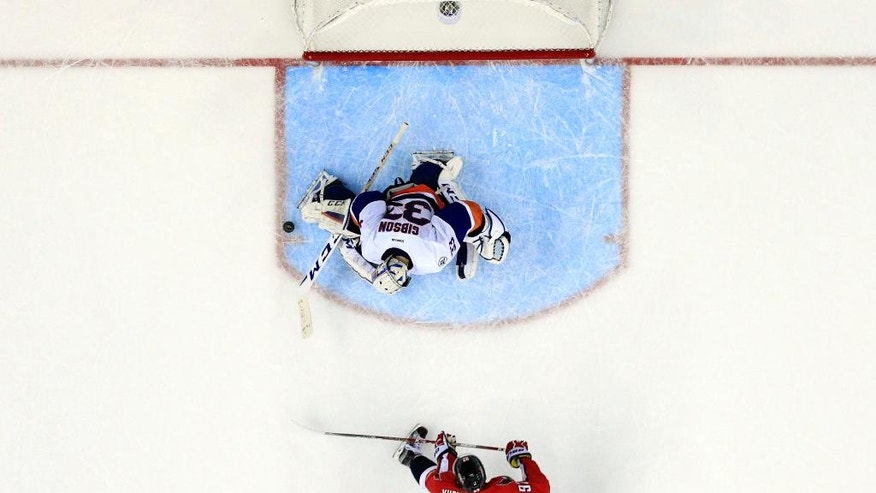 New York Islanders goalie Christopher Gibson (33), from Finland, blocks a shot by Washington Capitals center Evgeny Kuznetsov (92), from Russia, in the overtime period of an NHL hockey game, Tuesday, April 5, 2016, in Washington. The Islanders won 4-3 in overtime. (AP Photo/Alex Brandon)