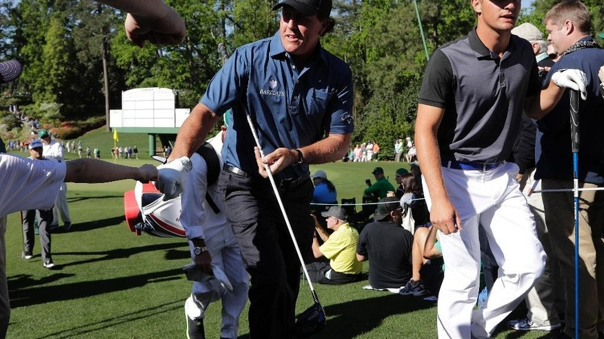 CORRECTS SPELLING TO DeCHAMBEAU, INSTEAD OF DeCHAMBEA - Phil Mickelson walks with amateur Bryson DeChambeau to the sixth tee during a practice round for the Masters golf tournament, Tuesday, April 5, 2016, in Augusta, Ga. (AP Photo/Jae C. Hong)