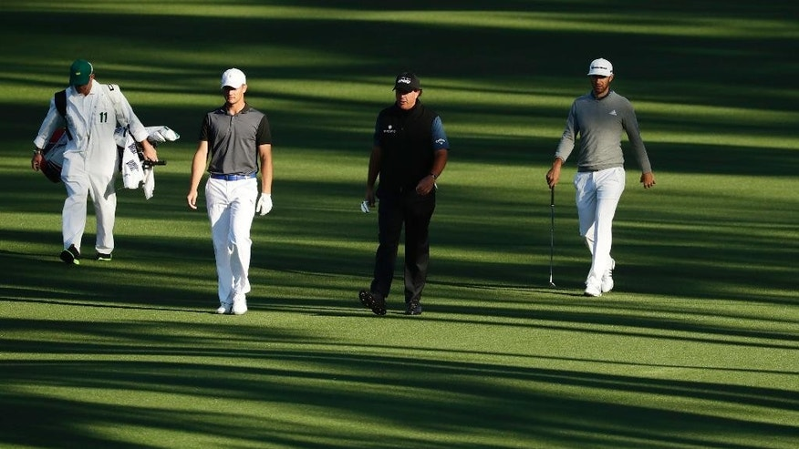 CORRECTS SPELLING TO DeCHAMBEAU, INSTEAD OF DeCHAMBEA - Amateur Bryson DeChambeau, second left, walks with Phil Mickelson and Dustin Johnson, right, down the second fairway during a practice round for the Masters golf tournament, Tuesday, April 5, 2016, in Augusta, Ga. (AP Photo/Charlie Riedel)