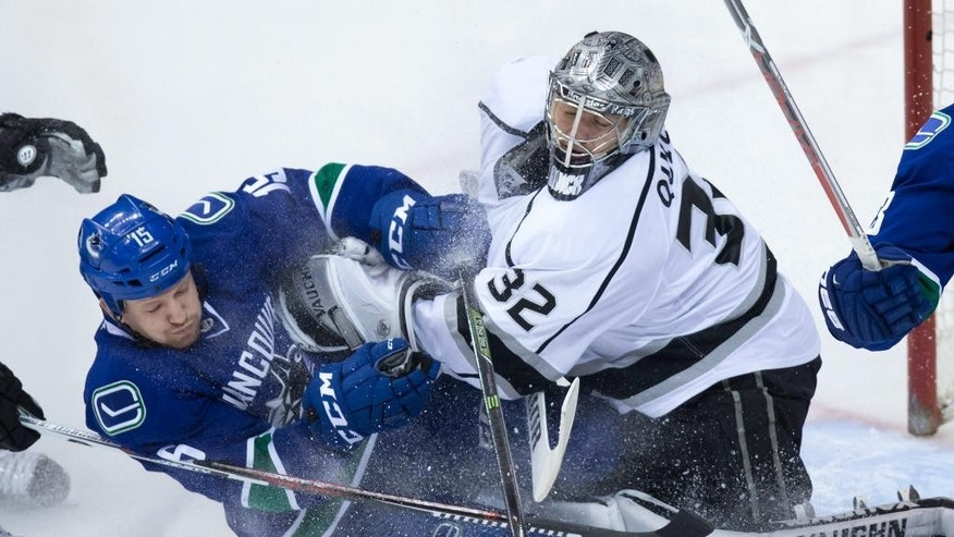 Vancouver Canucks' Derek Dorsett, left, crashes into Los Angeles Kings' goalie Jonathan Quick during the second period of an NHL hockey game in Vancouver, Canada, Monday, April 4, 2016. (Darryl Dyck/The Canadian Press via AP) MANDATORY CREDIT