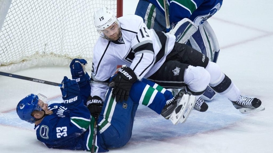 Los Angeles Kings' Andy Andreoff, top, falls on Vancouver Canucks' Henrik Sedin, of Sweden, during the second period of an NHL hockey game in Vancouver, Canada, Monday, April 4, 2016. (Darryl Dyck/The Canadian Press via AP) MANDATORY CREDIT