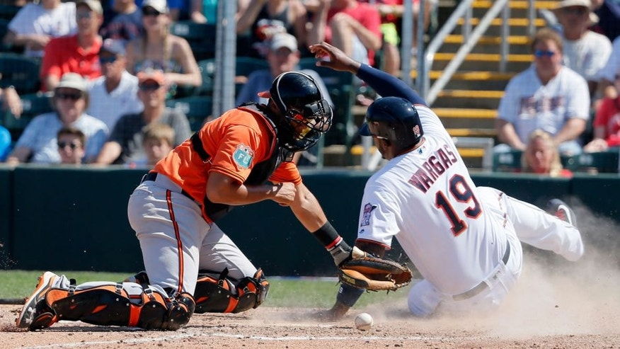 Baltimore Orioles catcher Francisco Pena is unable to hold on to the ball as Minnesota Twins' Kennys Vargas scores on a single by James Beresford in the sixth inning of a spring training baseball game, Sunday, March 13, 2016, in Fort Myers , Fla. The Twins won 14-5.