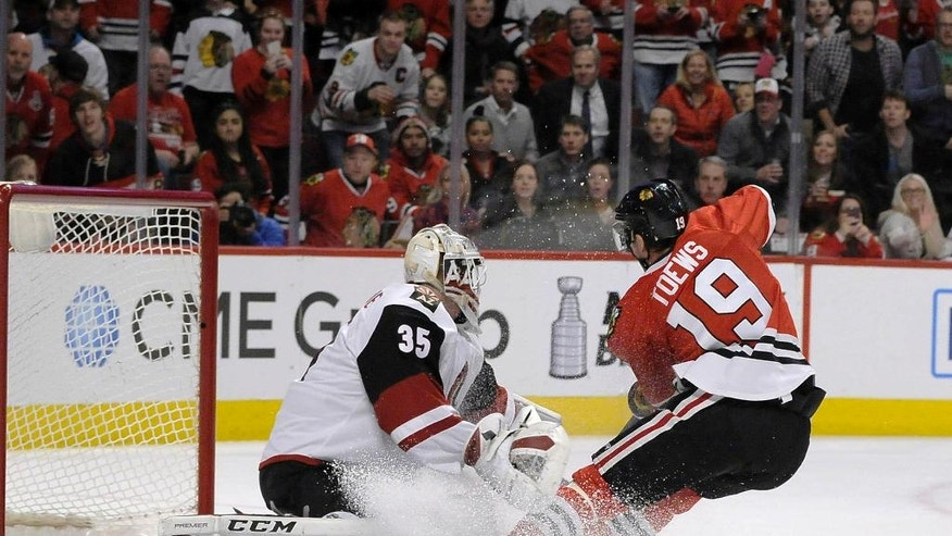 Chicago Blackhawks center Jonathan Toews (19) scores a goal on Arizona Coyotes goalie Louis Domingue (35) in the first period of an NHL hockey game Tuesday, April 5, 2016, in Chicago. (AP Photo/David Banks)