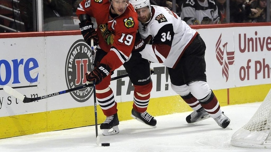 Chicago Blackhawks center Jonathan Toews (19) is defended by Arizona Coyotes defenseman Klas Dahlbeck (34) in the first period of an NHL hockey game Tuesday, April 5, 2016, in Chicago. (AP Photo/David Banks)