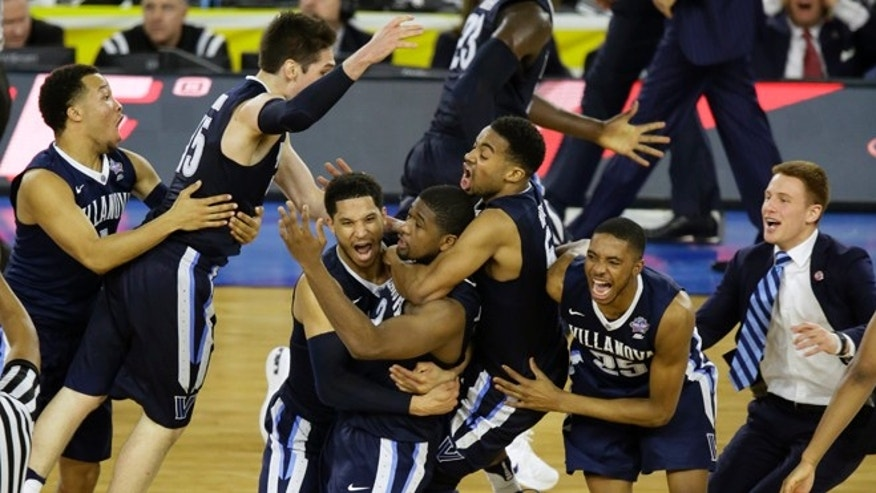Villanova players celebrates after Kris Jenkins, center, scores a game winning three point basket in the closing seconds of NCAA Final Four tournament college basketball championship game Monday, April 4, 2016, in Houston. Villanova won 77-74. (AP Photo/Charlie Neibergall)