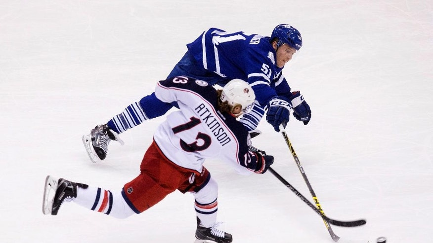 Toronto Maple Leafs defenseman Jake Gardiner, right, tries to block a shot from Columbus Blue Jackets right wing Cam Atkinson during the first period of an NHL hockey game, Wednesday,  April 6, 2016 in Toronto. (Chris Young/The Canadian Press via AP) MANDATORY CREDIT
