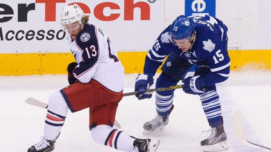 Columbus Blue Jackets right wing Cam Atkinson, left, battle for the puck against Toronto Maple Leafs right wing P.A. Parenteau during the first period of an NHL hockey game, Wednesday,  April 6, 2016 in Toronto. (Chris Young/The Canadian Press via AP) MANDATORY CREDIT