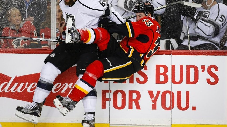 Los Angeles Kings' Jake Muzzin, left, checks Calgary Flames' Jakub Nakladal, from the Czech Republic, during the first period of an NHL hockey game, Tuesday, April 5, 2016 in Calgary, Alberta.  (Jeff McIntosh/The Canadian Press via AP) MANDATORY CREDIT
