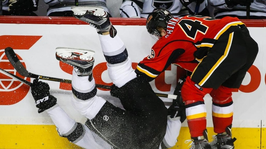 Los Angeles Kings' Jake Muzzin, left, is upended by Calgary Flames' Hunter Shinkaruk during the first period of an NHL hockey game, Tuesday,  April 5, 2016 in Calgary, Alberta.  (Jeff McIntosh/The Canadian Press via AP) MANDATORY CREDIT