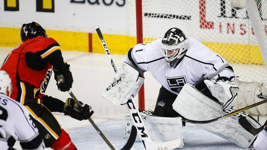 Los Angeles Kings goalie Jhonas Enroth, right, of Sweden, faces down Calgary Flames' T. J. Brodie during the second period of an NHL hockey game, Tuesday, April 5, 2016 in Calgary, Alberta.  (Jeff McIntosh/The Canadian Press via AP) MANDATORY CREDIT