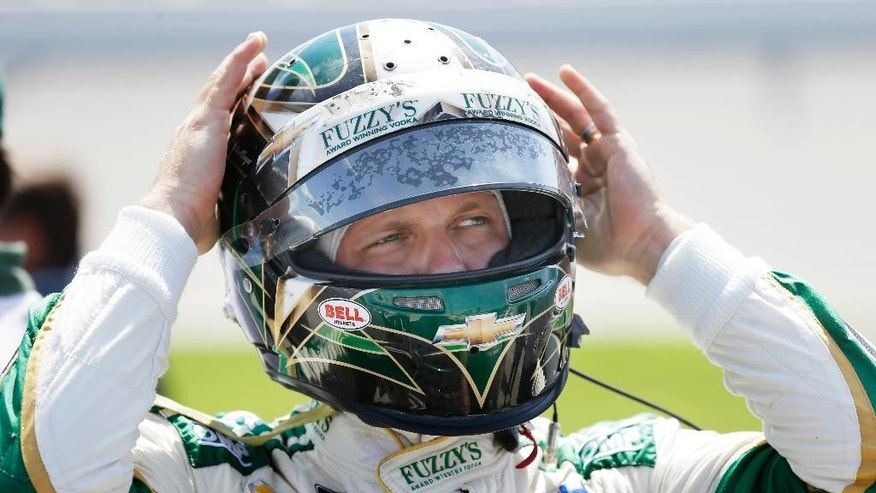 FILE - In this July 18, 2015, file photo, Ed Carpenter puts on his helmet during qualifying for the IndyCar Series auto race at Iowa Speedway in Newton, Iowa. Ed Carpenter and James Hinchcliffe left Indianapolis Motor Speedway on Wednesday, April 6, 2016, more confident about the cars they'll race in May. A new rear-wing flap should prevent cars from going airborne, as Carpenter experienced 11 months ago. New suspension parts should prevent drivers from getting gouged, which happened to Hinchcliffe last year at Indy. And as everyone tries to figure out what impact the new aerodynamic package might make, Carpenter and Hinchcliffe believe the racing will be safer.(AP Photo/Charlie Neibergall, File)