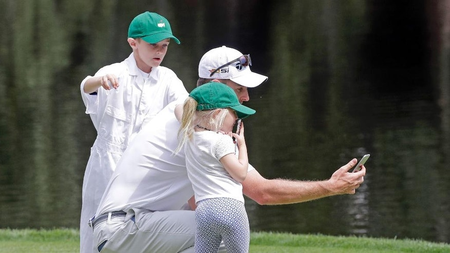 Justin Rose, of England, takes a selfie with his two children Leo and Charlotte during the par three competition at the Masters golf tournament Wednesday, April 6, 2016, in Augusta, Ga. (AP Photo/Jae C. Hong)