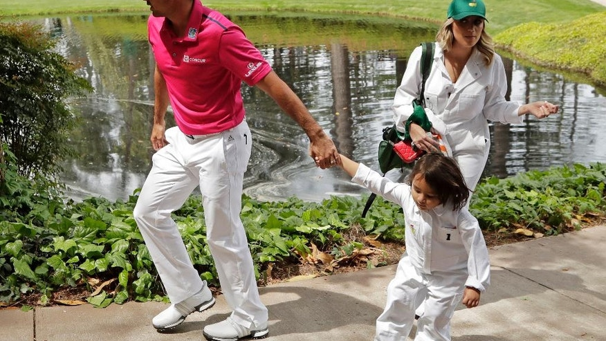 Jason Day, of Australia, walks to the ninth tee with son Dash and his wife Ellie Harvey during the par three competition at the Masters golf tournament Wednesday, April 6, 2016, in Augusta, Ga. (AP Photo/Charlie Riedel)
