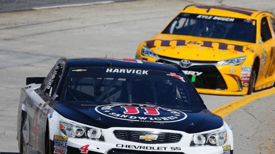 Driver Kevin Harvick (4) leads Kyle Busch (18) into Turn 4 during the Sprint Cup auto race at Martinsville Speedway on Sunday, April 3, 2016, in Martinsville, Va. (AP Photo/Steve Helber)