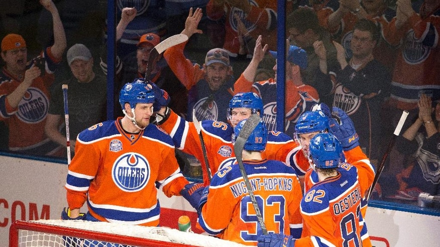 Edmonton Oilers celebrate a goal against the Vancouver Canucks during the third period of an NHL hockey game Wednesday, April 6, 2016, in Edmonton, Alberta. The Oilers won 6-2. (Jason Franson/The Canadian Press via AP)