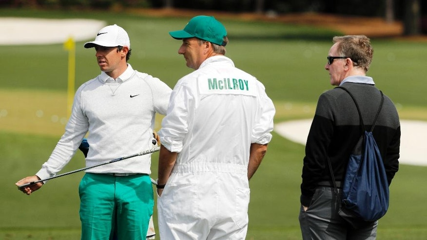 Coach Michael Bannon, right and caddie Jean-Paul Fitzgerald watch as Rory McIlroy, of Northern Ireland, during a practice round for the Masters golf tournament Wednesday, April 6, 2016, in Augusta, Ga. (AP Photo/Chris Carlson)